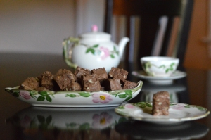 dish filled with fudge squares with teapot in background