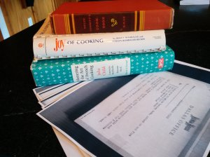 a pile of cookbooks: The Joy of Cooking, Mastering the Art of French Cooking, and Helen Corbitt Cooks