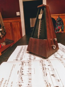 a pyramid metronome sitting on an open book of piano music